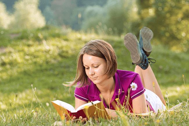 Jente leser bok i gresset.Foto.