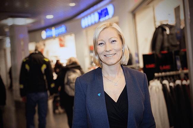 Ingeborg Flønes foran butikker. Foto.