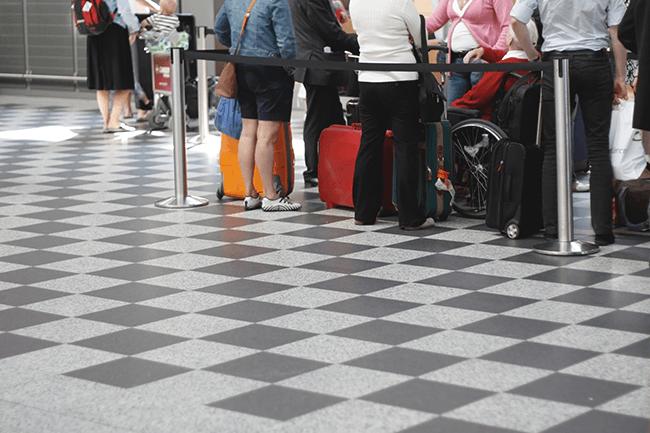 Folk venter i kø på flyplass. Foto.