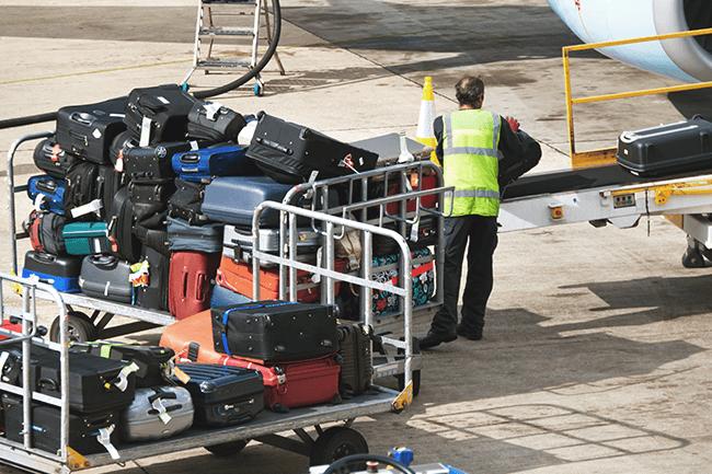 Mann lesser på bagasje på fly. Foto.