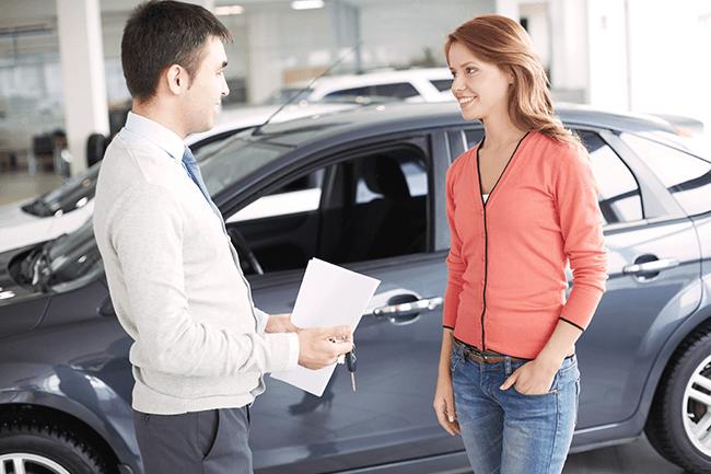 Kvinne prater med mann om bil. Foto.