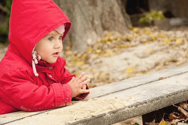 Liten unge med rød jakke. Foto.