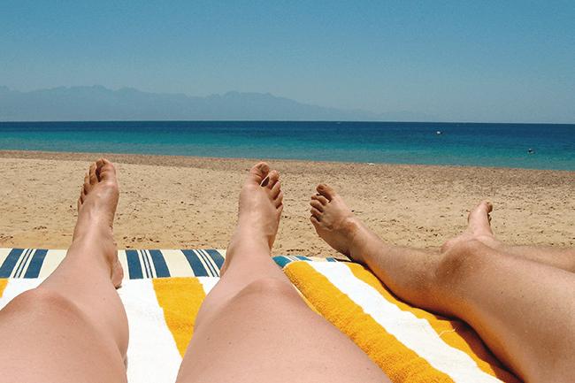 Par soler seg på stranda. Foto.