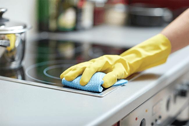 Person rengjør ovn på kjøkkenet. Foto.