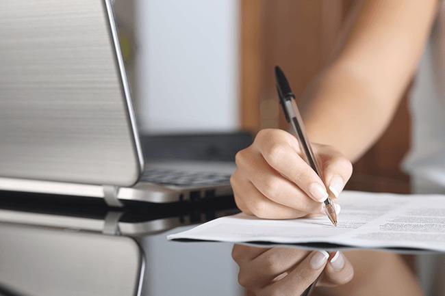 Kvinne skriver på papir. Foto.