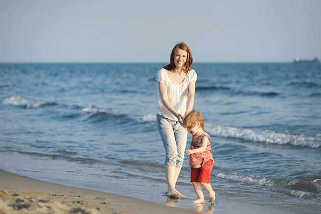 Mor og barn på stranda. Foto.