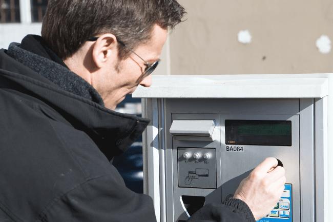 Mann betaler på parkeringsautomat. Foto.