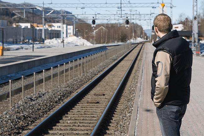 Mann venter på toget.Foto.