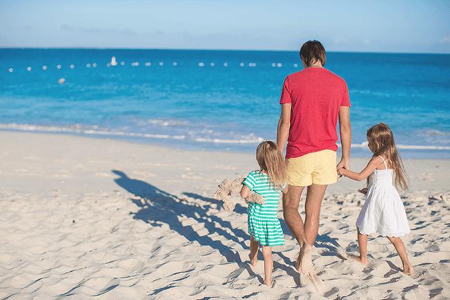 Far og to barn på stranda. Foto.