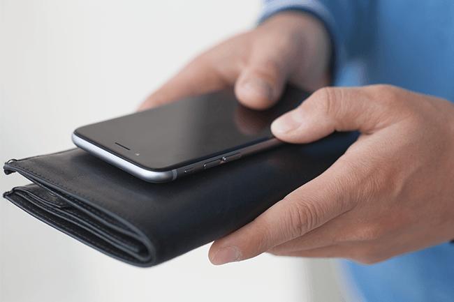 Mann holder lommebok og mobil.Foto.