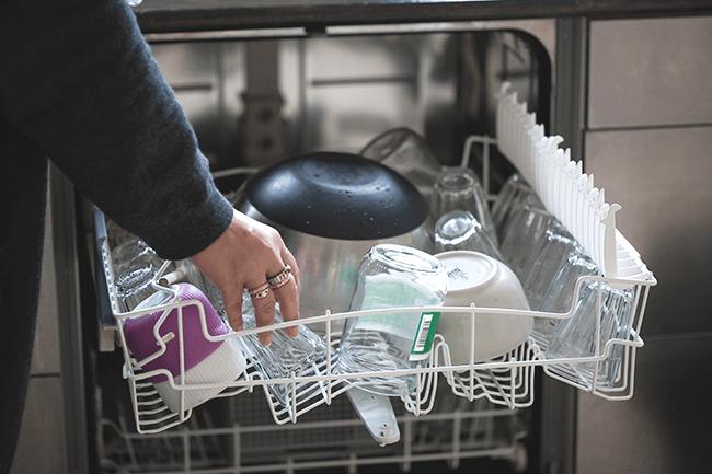 Kvinne åpner oppvaskmaskin. Foto.