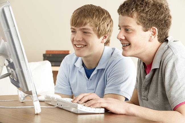 To unge gutter ser på dataskjerm.Foto.