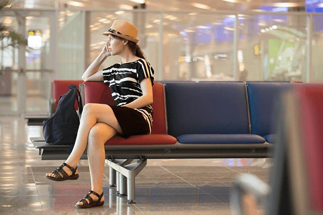 Kvinne venter på flyplassen. Foto.