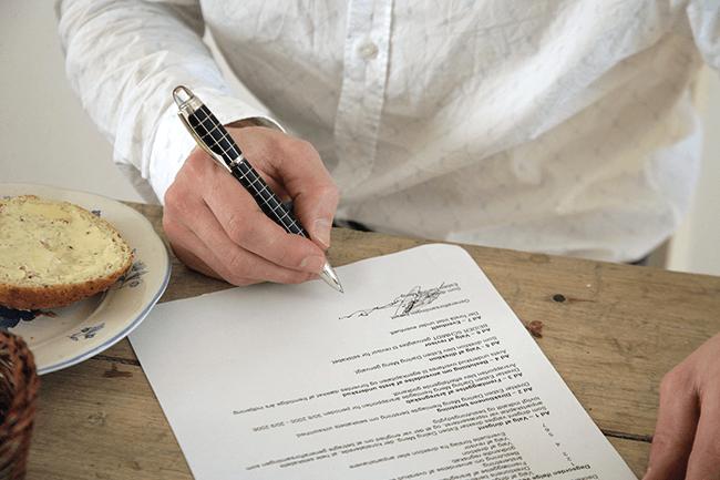 Mann skriver under på papir. Foto.