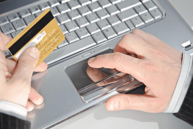 Mann betaler med kredittkort på nett. Foto.