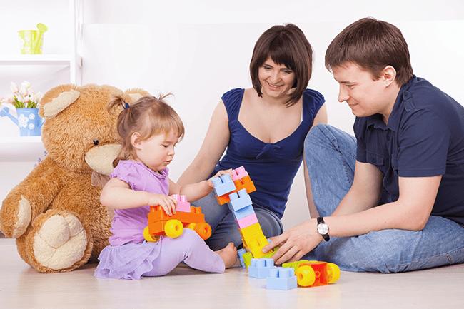 Par med en liten jente som leker. Foto.