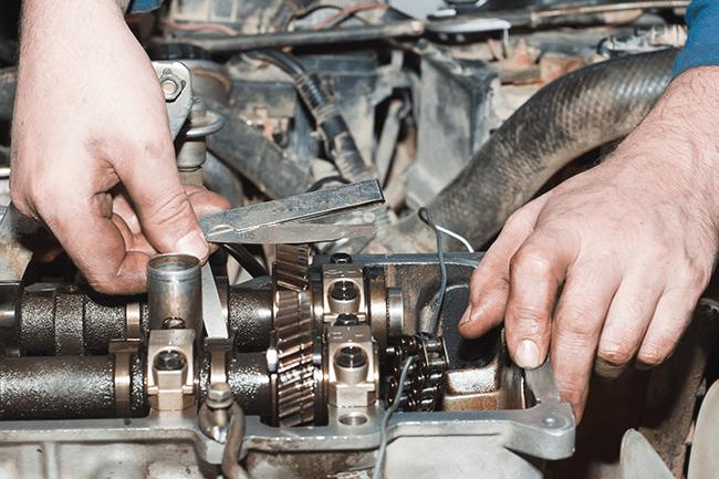 Mann reparerer bil. Foto.