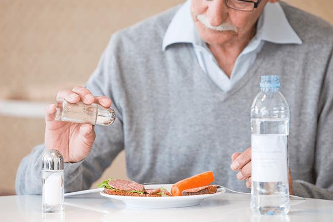 Eldre mann spiser. Foto.