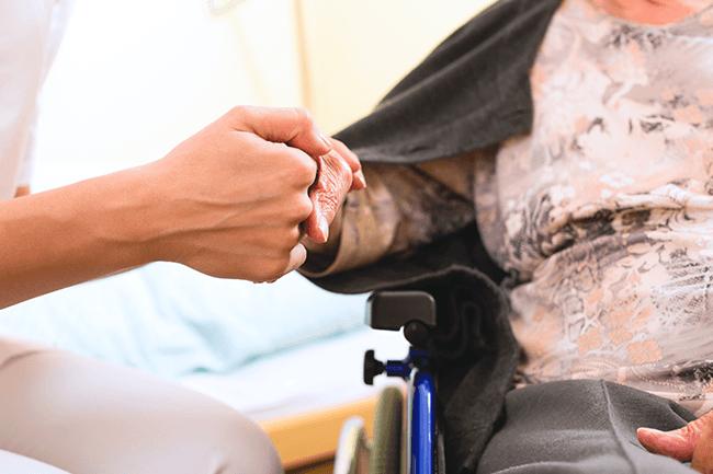 Sykepleier holder gammel dame i hånden. Foto.