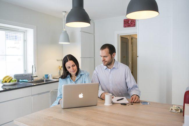 Mann og kvinne sitter på kjøkken.Foto