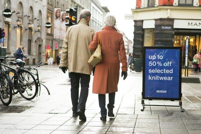 To voksne som går forbi salgsplakat i byen - Black Friday