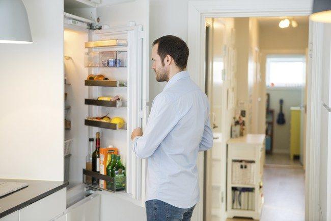 Mann som står med åpen kjøleskapsdør