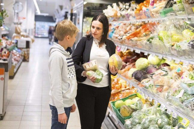 Foto av gutt og kvinne som holder grønnsaker i en butikk.