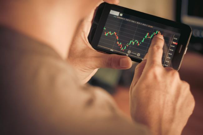 Sjekker børskurs på mobiltelefon.Foto