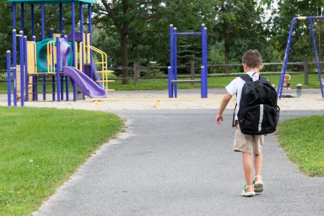 Barn med skolesekk.Foto