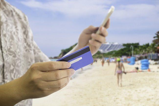 Turist på strand med kredittkort