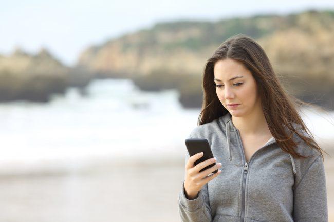 Tris, ung kvinne holder mobiltelefon.Foto