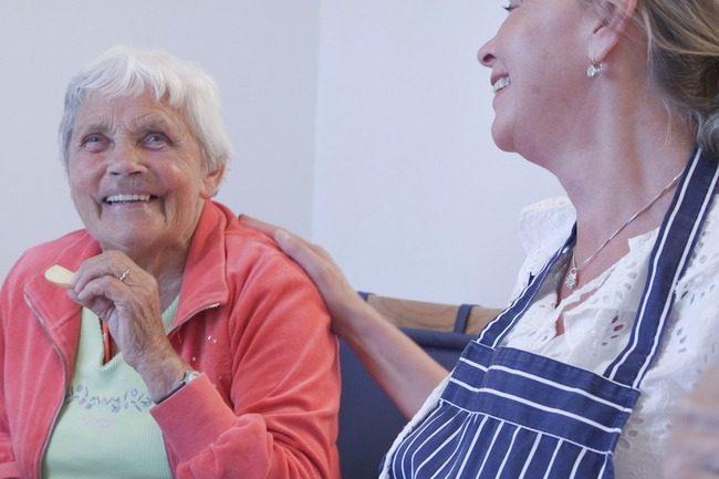 Eldre dame og ansatt på sykehjem.Foto