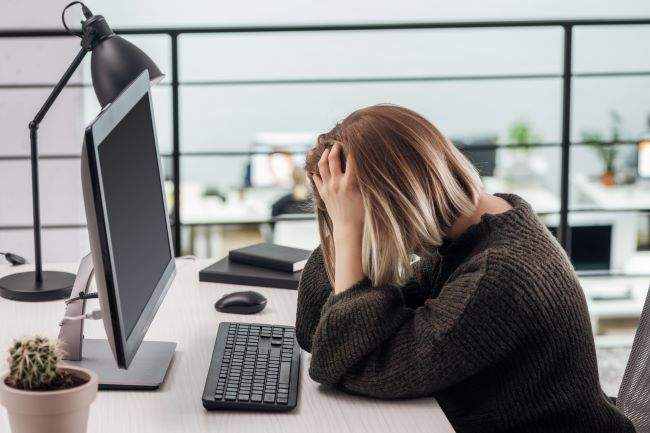 Trist kvinne foran PC.Foto